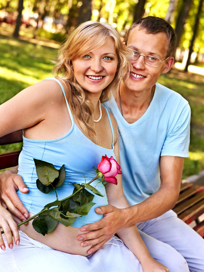 Pregnant woman with man outdoor. Pregnant woman, holding flower with men outdoor in park stock photo