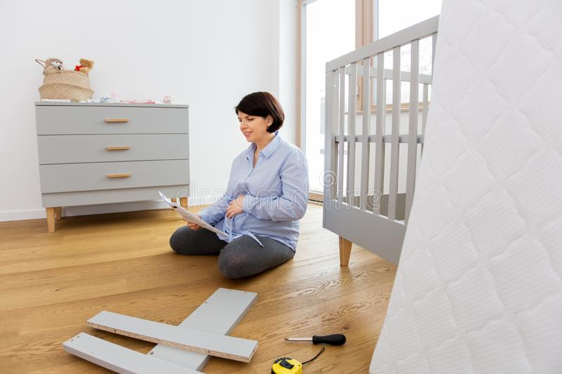 Pregnant woman with manual assembling baby bed. Pregnancy, nursery and people concept - single middle-aged pregnant woman with user manual assembling baby bed at stock image