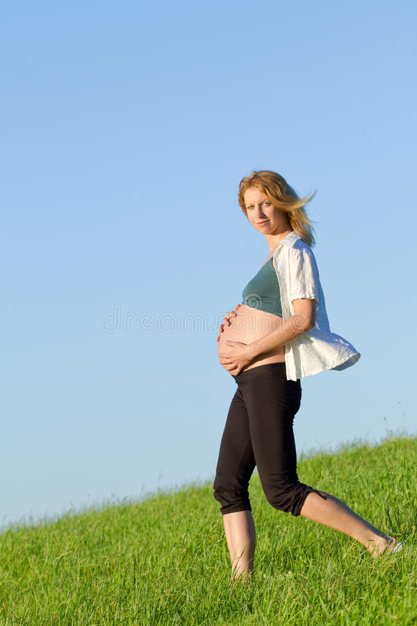 Download Pregnant woman on meadow stock photo. Image of femininity - 20636608