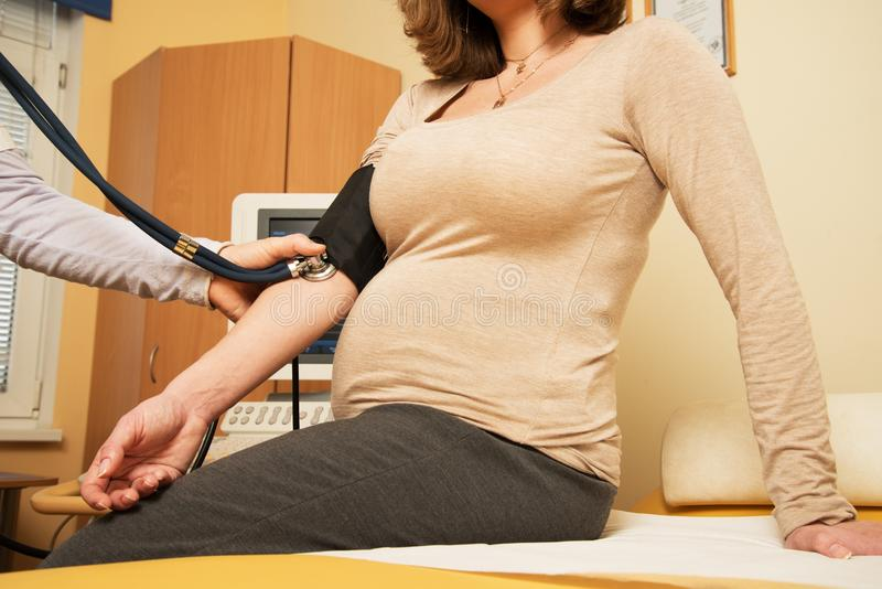 Pregnant woman measuring blood pressure stock images
