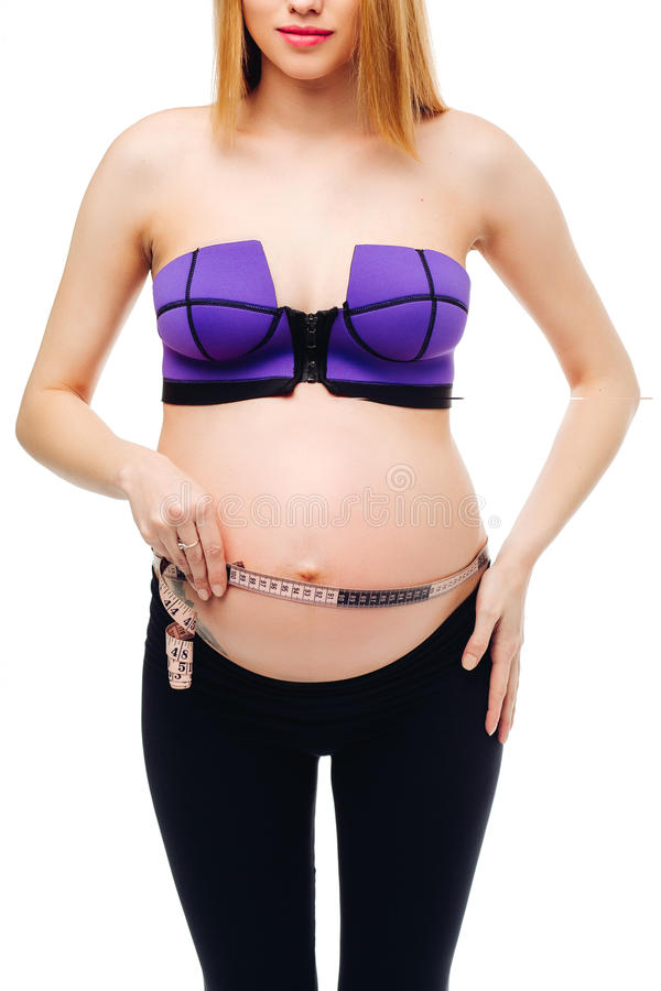 Pregnant woman measuring her big pregnant belly with measuring families. Mom Is Expecting A Baby. The concept of royalty free stock photos