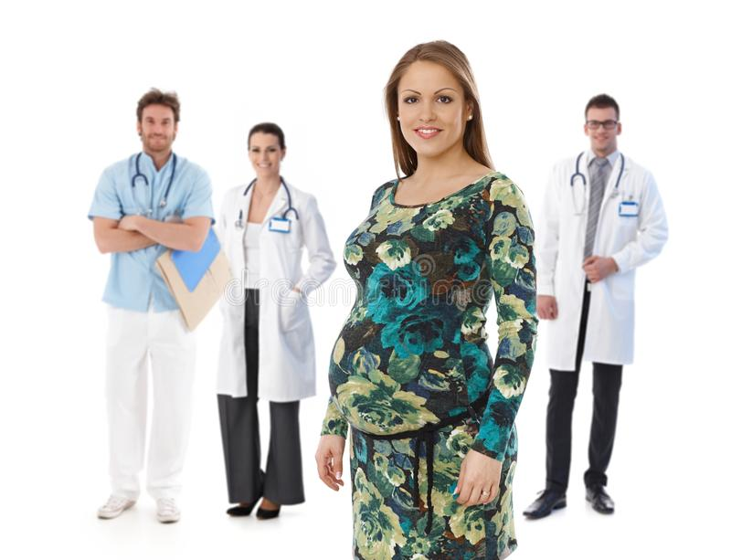 Pregnant woman with medical team in background. Portrait of happy young pregnant women with medical team in background, isolated on white background stock images