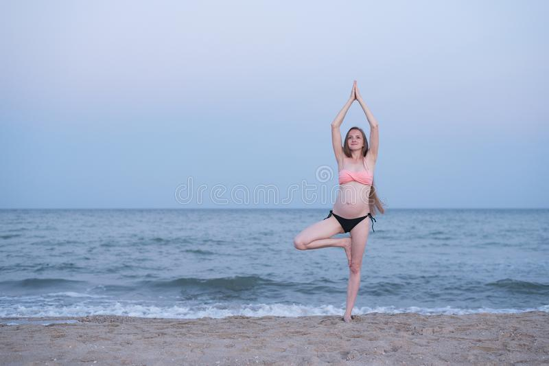 Pregnant woman meditates on the beach. Yoga practice. Soft evening light.  stock images