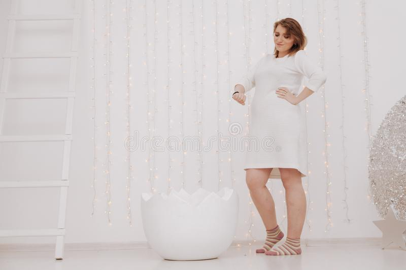 A pregnant woman at 9 months stands near a huge broken eggshell and waits for the baby to appear on a white background.  stock photography