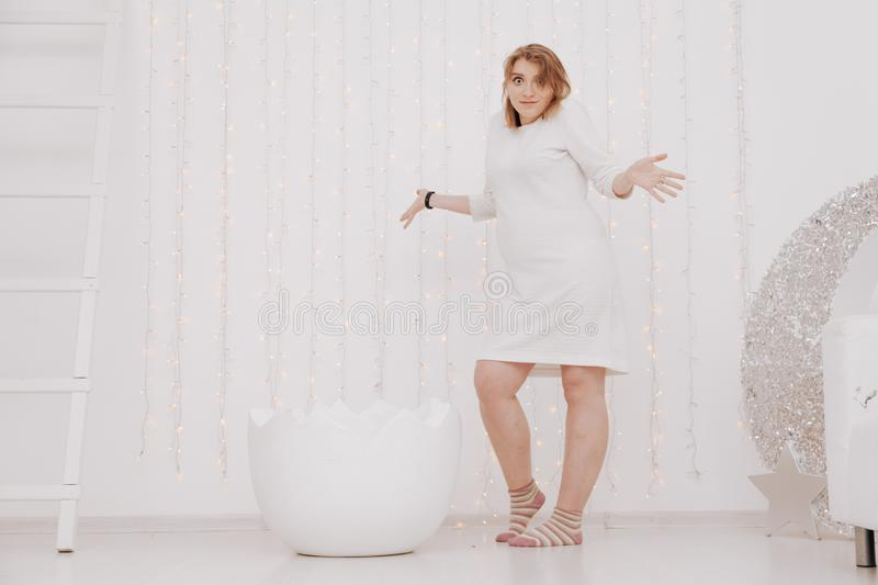 A pregnant woman at 9 months stands near a huge broken eggshell and waits for the baby to appear on a white background.  royalty free stock image