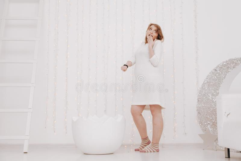 A pregnant woman at 9 months stands near a huge broken eggshell and waits for the baby to appear on a white background.  royalty free stock photos