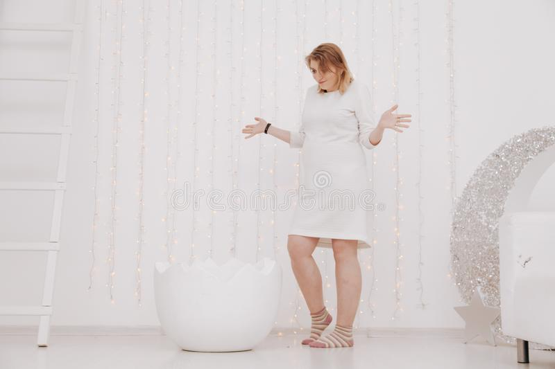 A pregnant woman at 9 months stands near a huge broken eggshell and waits for the baby to appear on a white background.  royalty free stock images