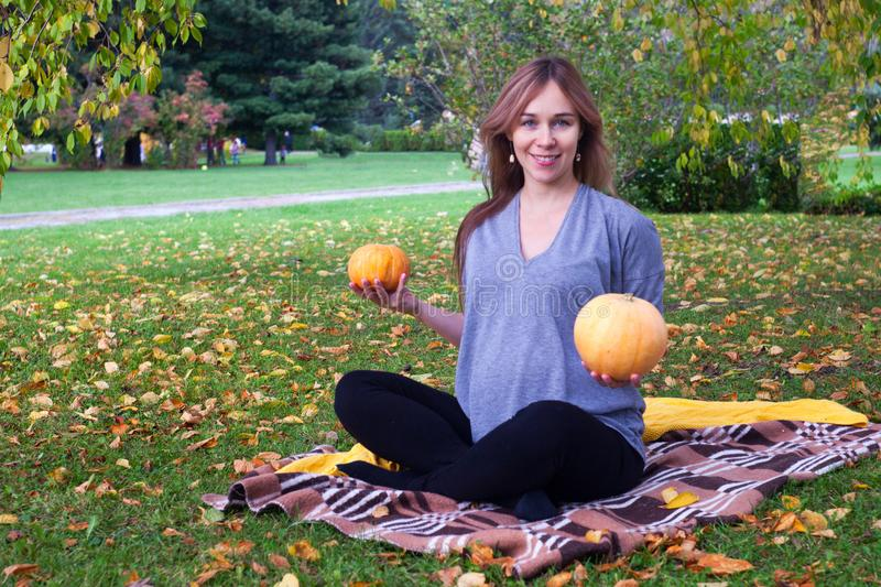 Pregnant woman on the nature holding two pumpkins in her hands, funny concept og prenancy, autumn time. royalty free stock image