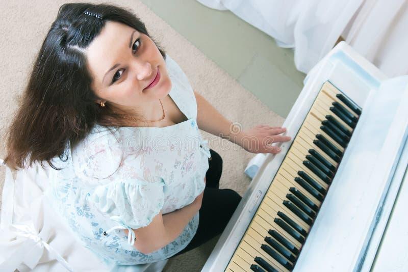 The pregnant woman near a piano stock photo