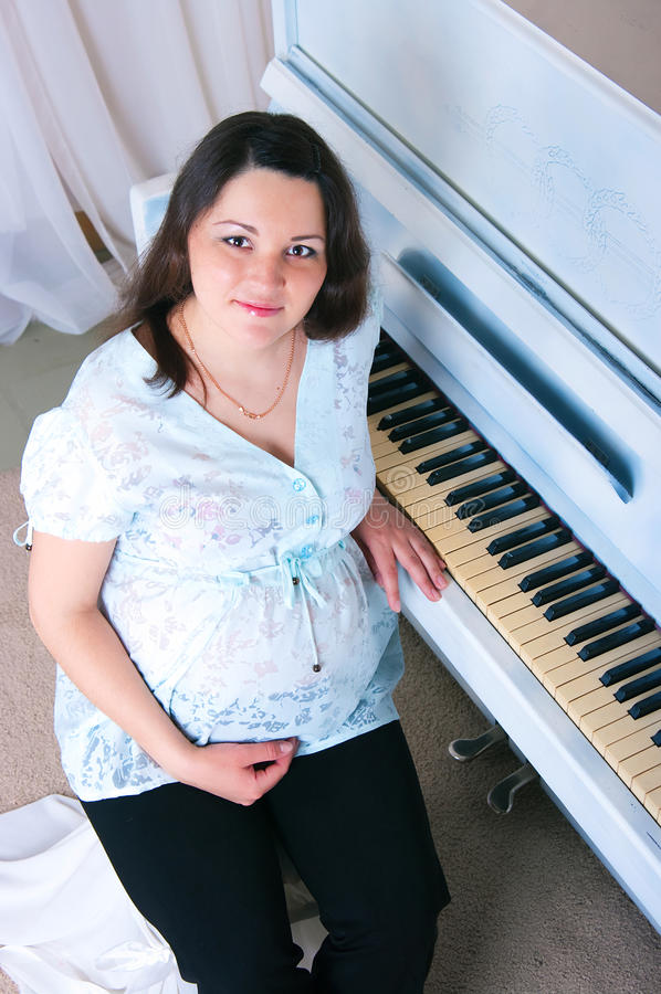 The pregnant woman near a piano stock images