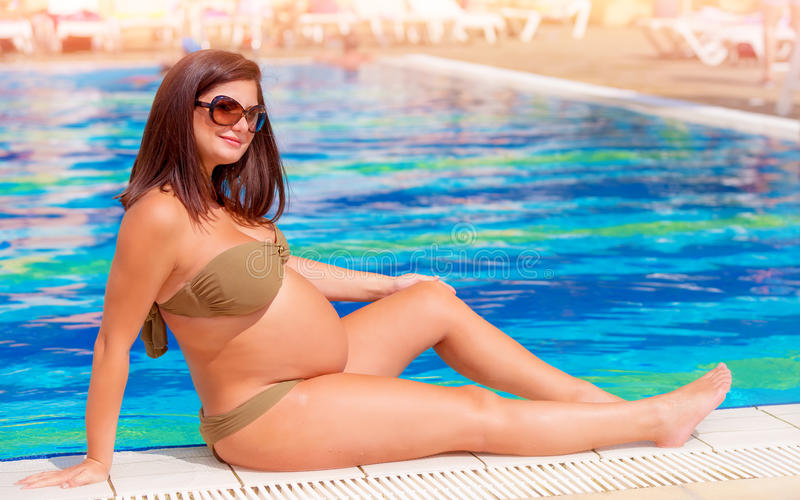 Pregnant woman near the pool royalty free stock photography