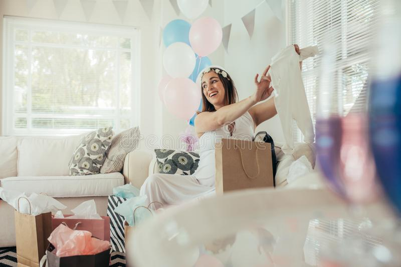 Pregnant woman with new gift at baby shower royalty free stock photos