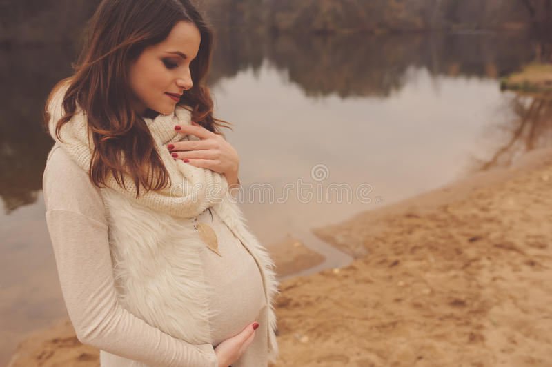 Pregnant woman on outdoor autumn walk, cozy warm mood stock photo