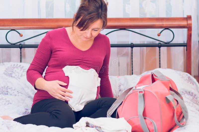Pregnant woman packing hospital bag royalty free stock photos