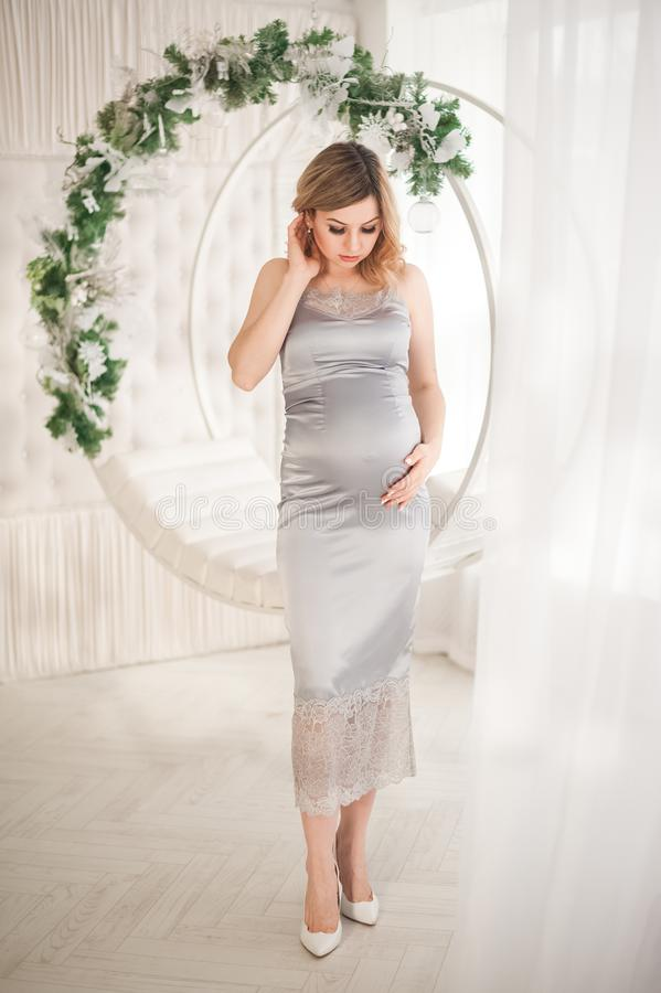 Pregnant woman in peignoir with swings that are decorated for the New Year close-up. A woman waiting for a baby in a silver dress royalty free stock photos