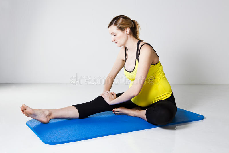 Pregnant woman performing leg stretch royalty free stock image