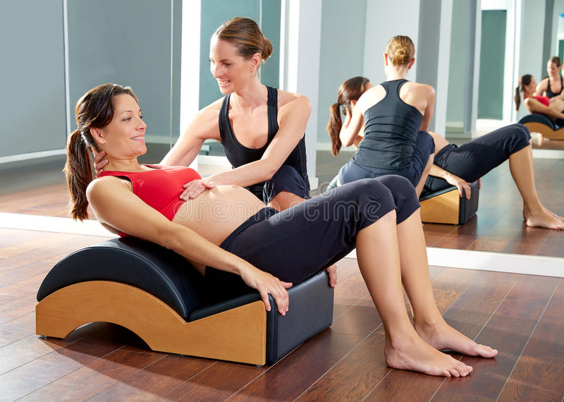 Pregnant woman pilates exercise roll back stock photo