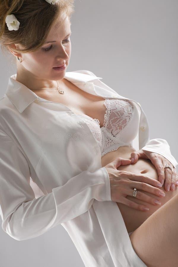 Pregnant woman portrait. Fine-art portrait of a pregnant woman on gray background stock photo