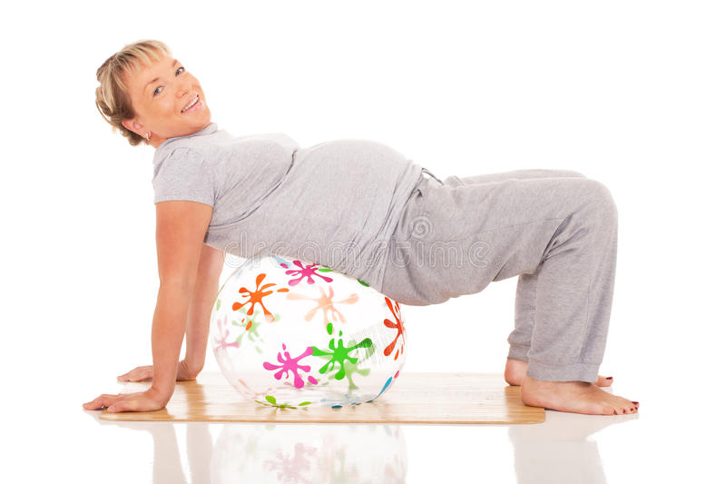 Pregnant woman practices yoga. Feature mother doing gymnastic exercises on isolated white background royalty free stock photography