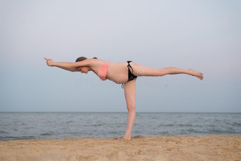 Pregnant woman practicing yoga on the beach. Soft evening light.  royalty free stock image