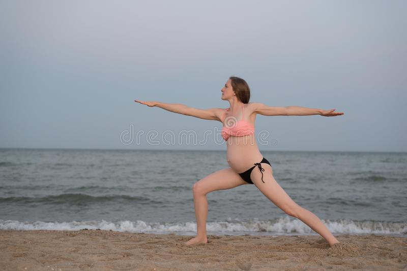 Pregnant woman practicing yoga on the beach. Soft evening light.  royalty free stock images