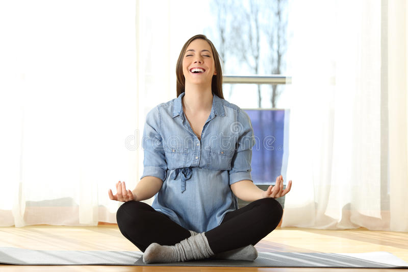 Pregnant woman practicing yoga exercises at home stock photography