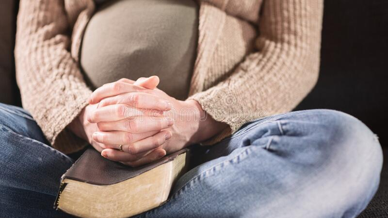 Pregnant Woman Praying at Home with Hands over a Bible royalty free stock photography