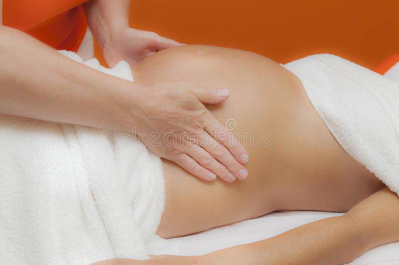 Pregnant woman at prenatal massage, glamour clarity effect. Pregnant young latina woman with beautiful skin, being wrapped with a towel, lying on a bed and stock photography