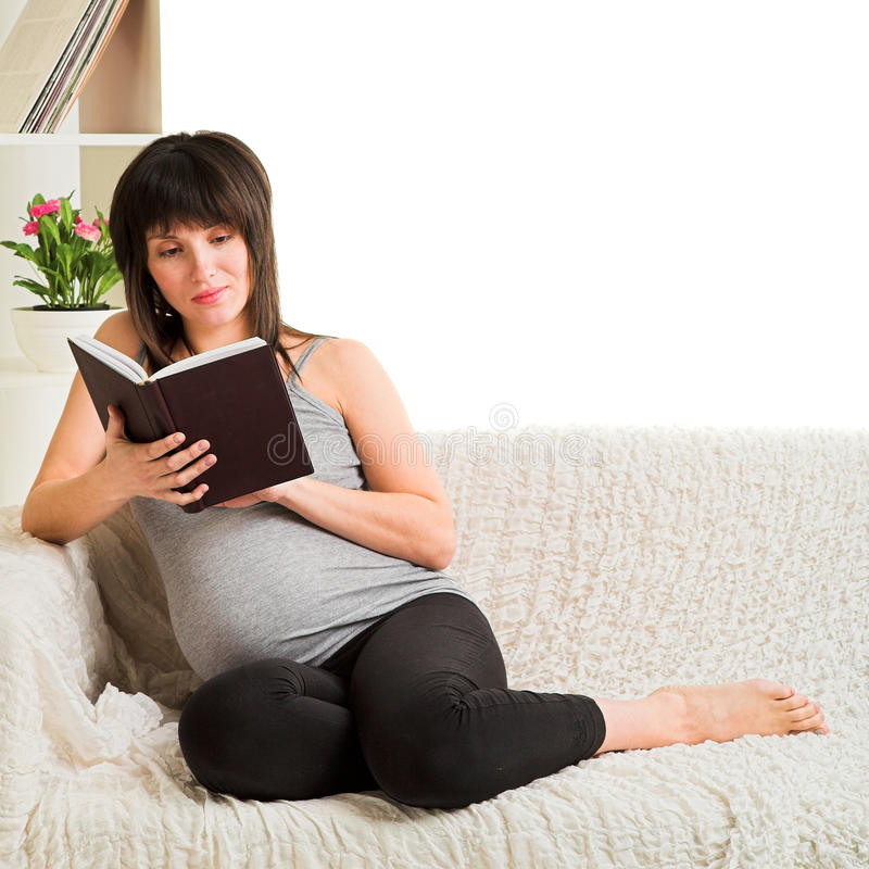 Pregnant woman reading book stock photography