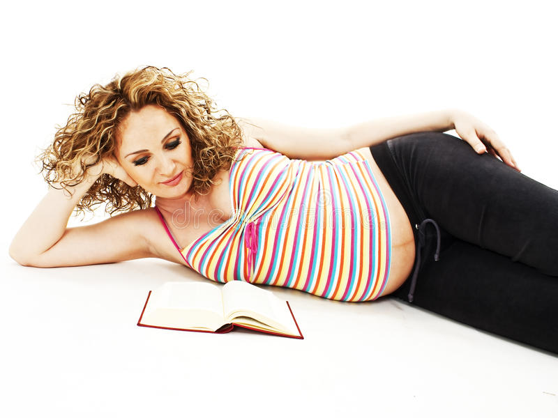 The pregnant woman reads the book stock photos