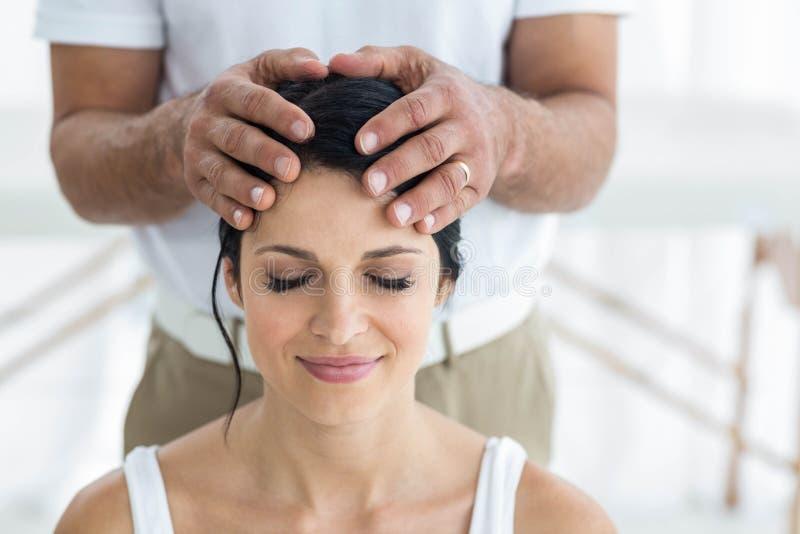 Pregnant woman receiving a head massage from masseur stock photos