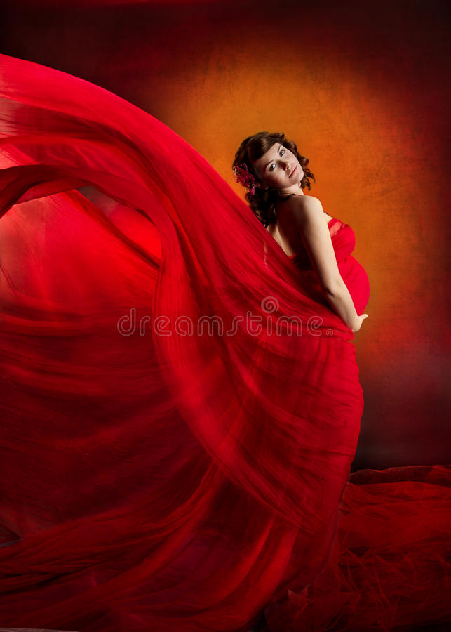 Pregnant woman in red flying waving dress. Pregnant woman in red waving flying dress. Looking at camera stock photos