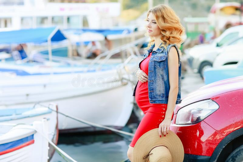 Pregnant woman in red shirt, hat, sunglasses and black trousers at yacht marina of Malta stock images
