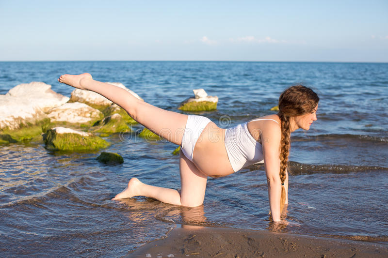Pregnant Woman In Relaxation On Yoga Pose On Sea Stock Photography