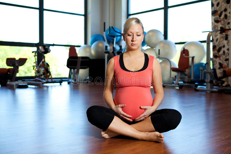 Pregnant woman relaxing and holding belly. stock image