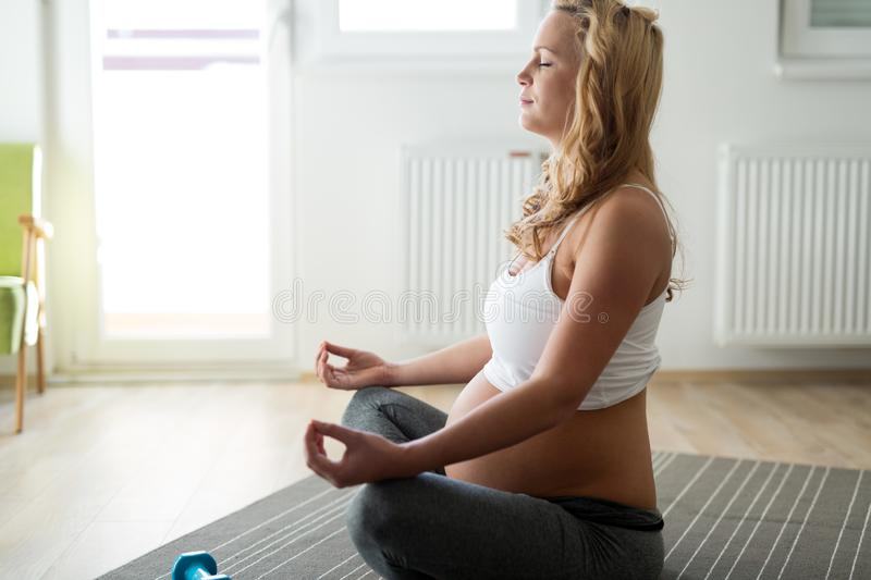 Pregnant woman relaxing and practicing yoga at home stock image