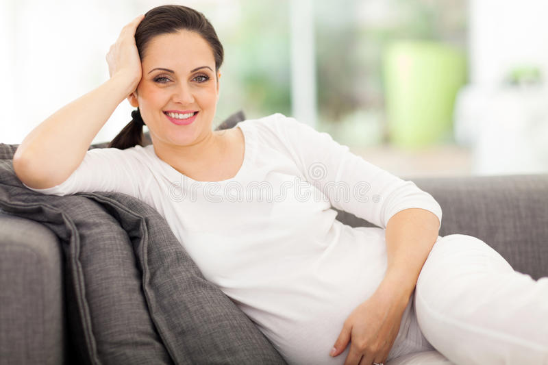 Pregnant woman resting. Beautiful pregnant woman resting on a sofa stock image
