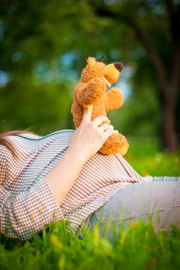 Pregnant woman's belly and teddy bear royalty free stock photos