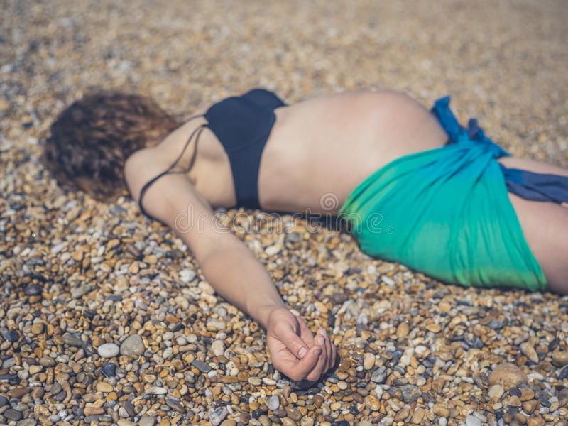 Pregnant woman in sarong lying on the beach. A pregnant woman wearing a sarong is lying on the beach royalty free stock photos