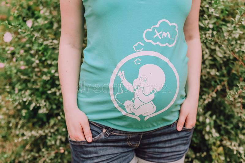 Pregnant woman shirt green with picture baby royalty free stock photo