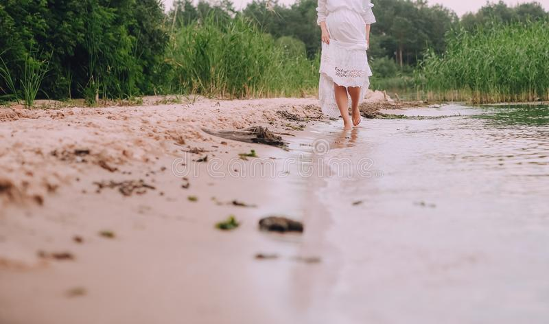 Pregnant woman shore river sand water stock photography