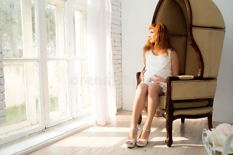 Pregnant woman sit on the fashion chair close to the window royalty free stock images