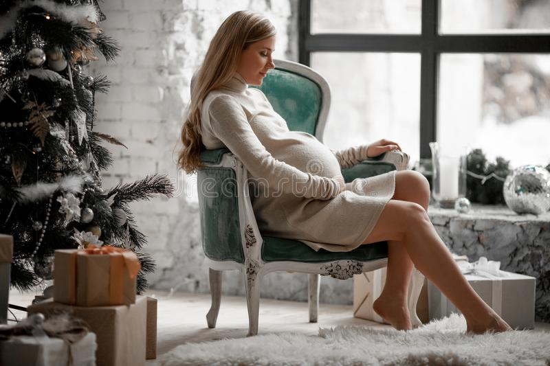 Pregnant woman sits in an armchair by the window next to Christmas tree. royalty free stock photos