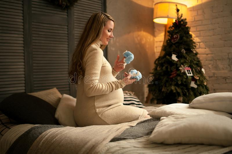 Pregnant woman sits before Christmas tree and looks at baby`s bo royalty free stock photography