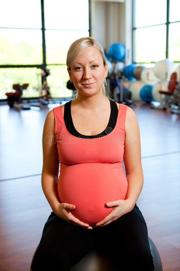 Pregnant woman sitting on ball holding belly. stock photography