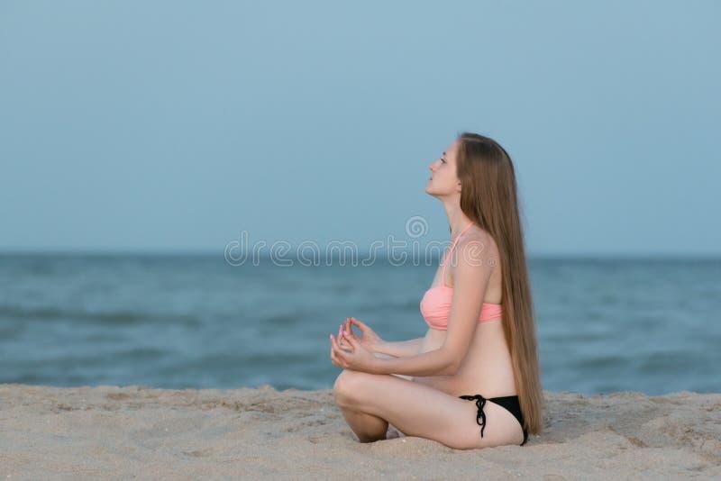 Pregnant woman sitting on a beach and meditates. Soft evening light, deserted beach.  stock photos