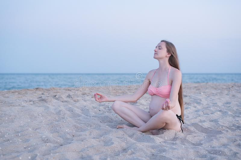 Pregnant woman sitting on a beach and meditates. Soft evening light, deserted beach.  royalty free stock photos