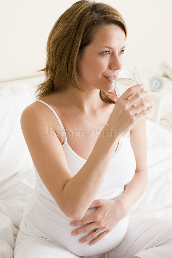 Pregnant woman sitting in bedroom with glass. Pregnant woman sitting in bed smiling stock images