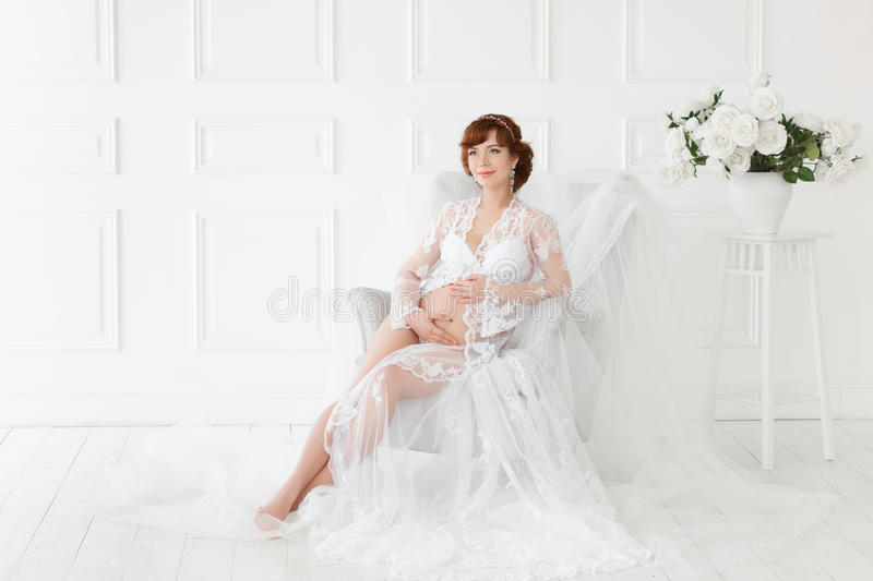 Pregnant woman sitting in a chair in a beautiful white dress boudoir . royalty free stock photography