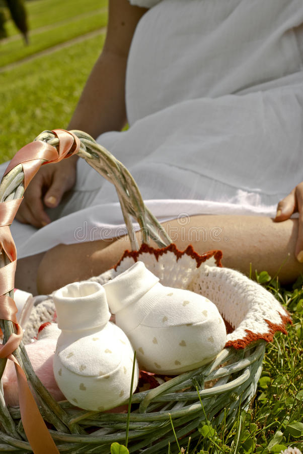 Pregnant woman is sitting on the grass. With a gift basket stock photos